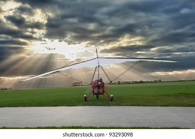 microlight against a clouds scape with light beams