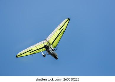 Microlight aircraft flying high against a deep blue sky.
