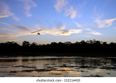 A microlight aircraft flying over a channel in the Okavango Delta in Botswana at sunset.