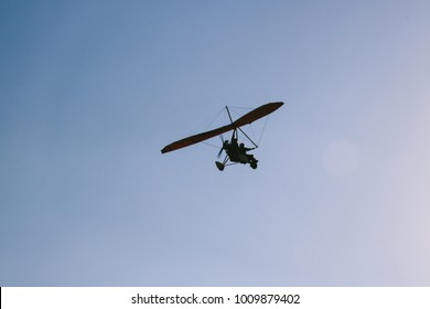 A microlight aircraft flying in the sky.