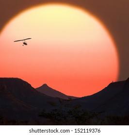 Microlight aircraft and a Namibian Sunset - Damaraland in northern Namibia