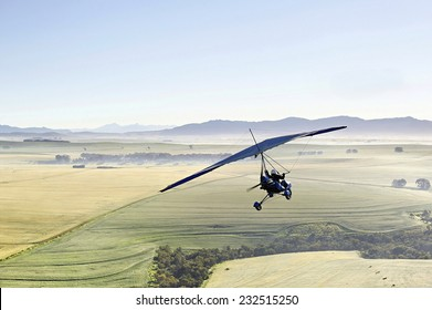 A microlight aircraft soars over the countryside