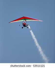 Microlight airplane with a smoke trail against blue sky