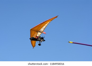 Microlight flying with a ribbon behind him