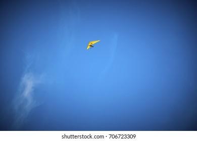 Microlight high in clear blue sky