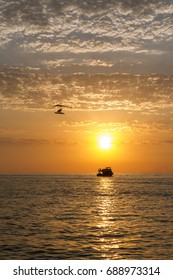 Microlight plane with Boat at the sunset