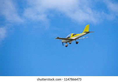 A microlight yellow and white aircraft flying on a blue sky with light white clouds in the background