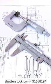 Micrometer and caliper on blueprint vertical. Shallow depth of field.