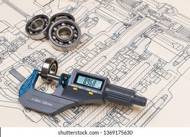 Micrometer screw gauge. Ball bearings. Drawing on background. Accurate measuring tool. Digital display. Round metal parts group. Engineering draft, plan, design. Education, study. Full depth of field.