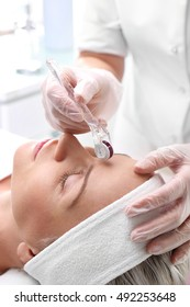 Microneedle mesotherapy, face lift. Beautician performs a needle mesotherapy treatment on a woman's face