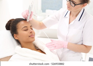 Microneedle mesotherapy.Beautician performs a needle mesotherapy treatment on a woman's face