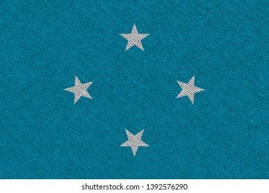 Micronesia fabric flag. Patriotic background. National flag of Micronesia