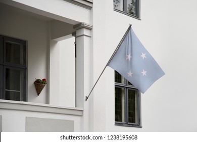 Micronesia flag hanging on a pole in front of the house. National flag waving on a home displaying on a pole on a front door of a building and raised at a full staff.