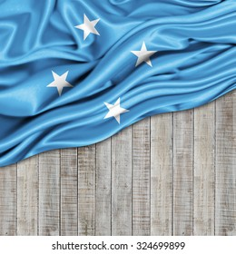 Micronesia   flag of silk with copyspace for your text or images and wood background