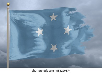 Micronesia Flag with torn edges in front of a stormy sky
