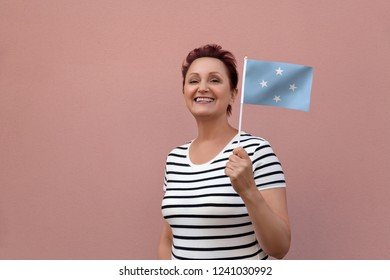 Micronesia flag. Woman holding Micronesia flag. Nice portrait of middle aged lady 40 50 years old with a national flag over pink wall background outdoors.