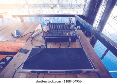 Microphone and audio mixer controller for football field with net in stadium.