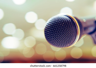 Microphone in the background with bright lights on the singing contest stage in vintage tone.