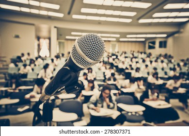 A microphone with blur background of many students learning