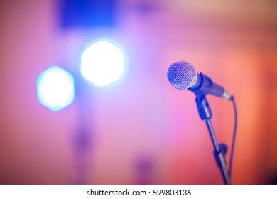 microphone with bokeh light in concert hall or conference room soft and blur style for background.Microphone over the Abstract blurred photo of conference hall or seminar room background.