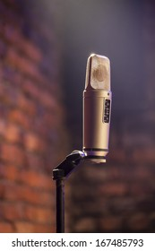 A microphone with a brick stage background