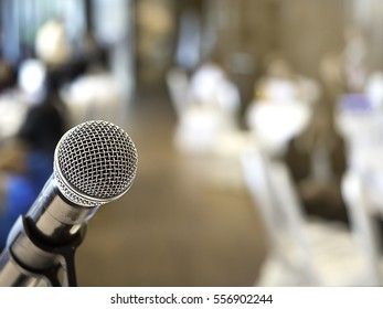 Microphone in business conference room or symposium hall with audience at the meeting room in out of focus blur background. Extremely shallow dof. Filtered process.