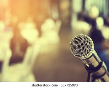 Microphone in business conference room or symposium hall with audience at the meeting room in out of focus blur background. Extremely shallow dof.  Vintage style and filtered process.