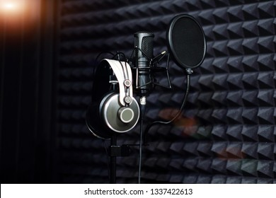 Microphone close - up on the background of a professional recording Studio. Workplace singers and musicians. Microphone stand and headphones for records vocals, speakers and sound of musical instrumen