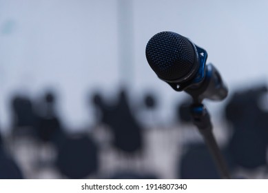 microphone close-up against the background of an empty hall with chairs