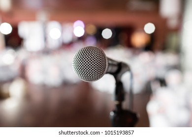 Microphone close-up. Focus on mic. Abstract blurred conference hall or wedding banquet on background. Event concept