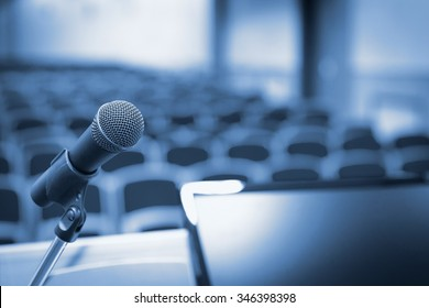 Microphone and computer in empty conference hall before speech