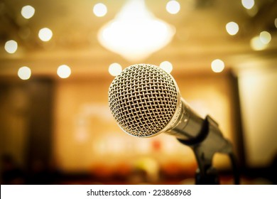 Microphone in concert hall or conference room with defocused bokeh lights  in background. Extremely shallow dof.