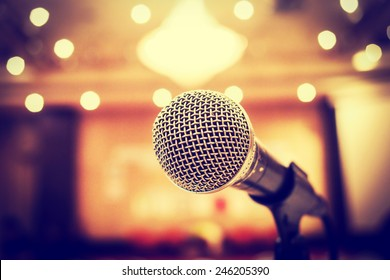 Microphone in concert hall or conference room with defocused bokeh lights  in background. Extremely shallow dof. : Vintage style