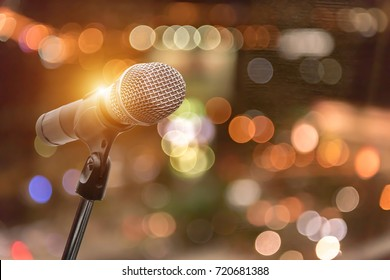 microphone in concert hall, restaurant or conference room blurred background.