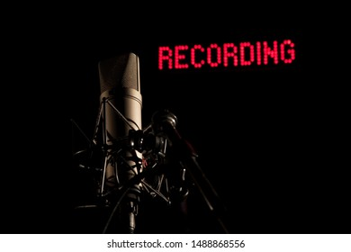 Microphone in dark studio in front of red recording backlit lettering