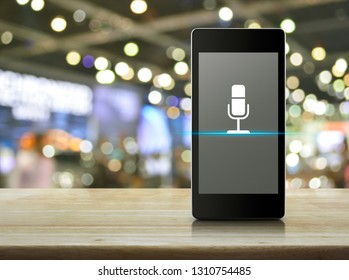 Microphone flat icon on modern smart mobile phone screen on wooden table over blur light and shadow of shopping mall, Business communication online concept