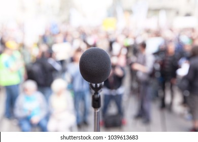 Microphone in focus, blurred crowd in the background. Political rally. Protest.