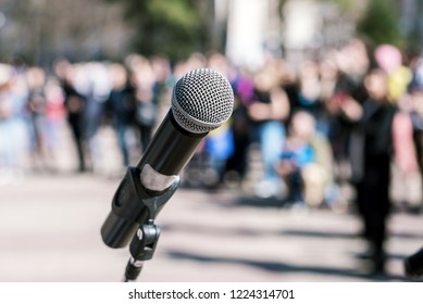 Microphone in focus and blurred crowd in the background at a political demonstration. rally. holiday concert. protest.
