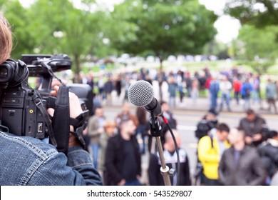 Microphone in focus, cameraman filming blurred crowd