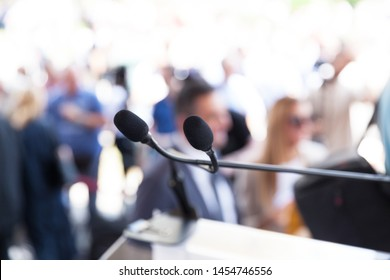 Microphone in focus at media or public event, blurred people in the background