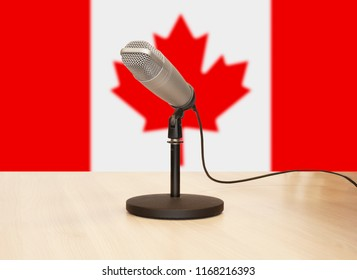 Microphone in front of the flag of Canada