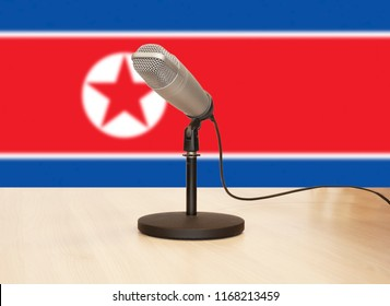 Microphone in front of the flag of North Korea
