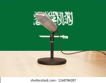 Microphone in front of the flag of Saudi Arabia