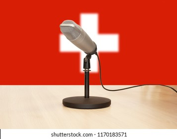 Microphone in front of the flag of Switzerland