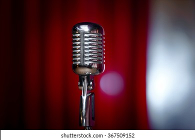 microphone in front of red curtain on an empty stage after the concert, smoke