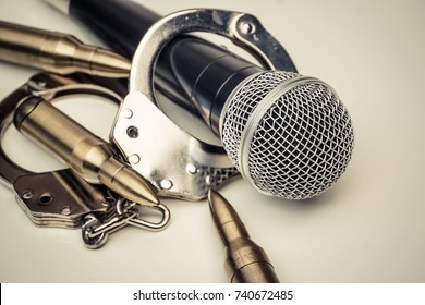 A microphone with handcuffs / Freedom of the press is at risk concept - World press freedom day concept