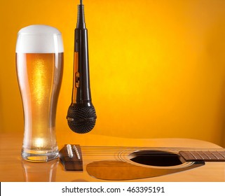 microphone hangs beside glass of beer on guitar. yellow background. empty space for text