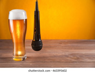 microphone hangs beside glass of beer. yellow background. empty space for text