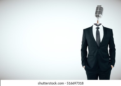 Microphone headed businessman on light background with copy space. Speech concept
