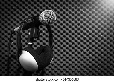 microphone & headphone on acoustic board background in recording studio